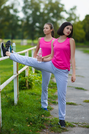 Two young woman doing gymnastic exercises outdoor