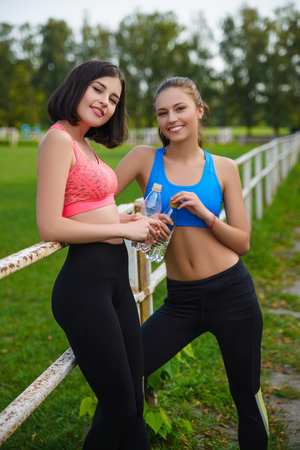 Beautiful fitness athlete girls resting or drinking water outdoor