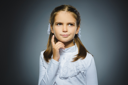 Closeup Thoughtful girl with Hand at head isolated on Gray Archivio Fotografico