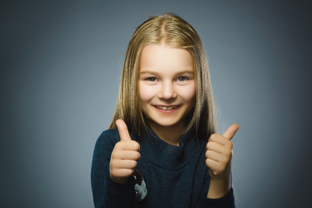 Happy girl showing thubs up. Closeup Portrait child smiling isolated on grey Zdjęcie Seryjne