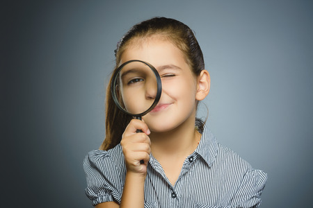 Girl See Through Magnifying Glass, Kid Eye Looking with Magnifier Lens over Gray