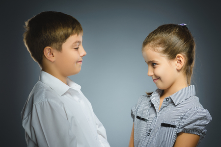 boy and girl are smiling at each other. Portrait children isolated on grey Zdjęcie Seryjne
