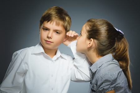 Teenage girl whispering in ear of boy on gray background. Communication concept
