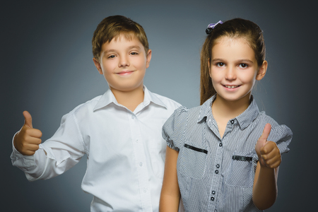 Happy girl and boy showing thubs up. Portrait children smiling isolated on grey
