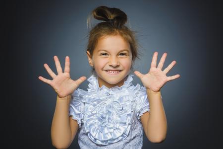 Happy girl. Closeup Portrait handsome child smiling isolated on grey Zdjęcie Seryjne