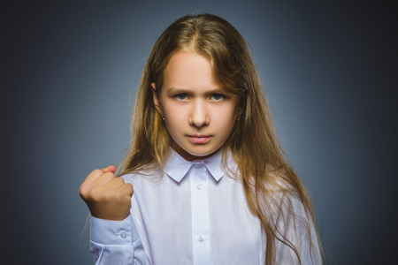 angry girl isolated on gray background.