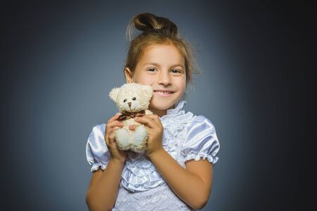 portrait of happy girl playing with teddy bear isolated on gray