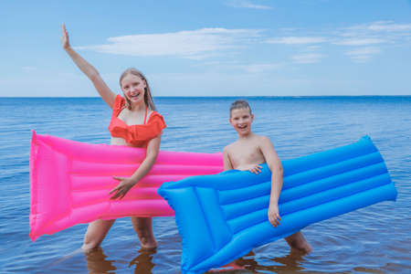 children bathe in inflatable mattresses in summer at sea