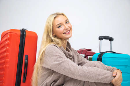 Traveling with a suitcase, happy, cheerful, beautiful blonde under an umbrella, white background, close-up.