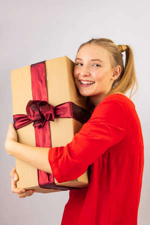 the girl is very happy and delighted with the box with gifts