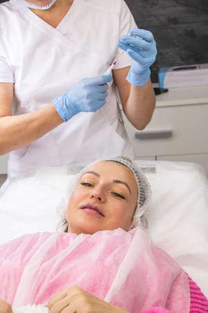 Cosmetology, lip augmentation, beauty injections in a beauty salon, close up