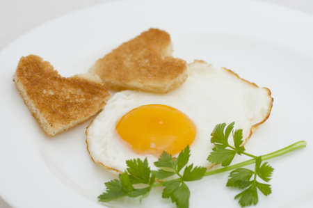 Fried egg with heart-shaped toasts with celery on white, romantic breakfast on St  Valentine s Day photo