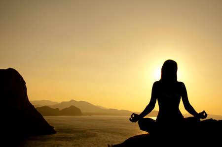Yoga Lotussitz Silhouette auf Meer bei Sonnenaufgang Lizenzfreie Bilder