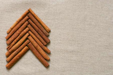 Christmas tree made of cinnamon sticks on linen background photo