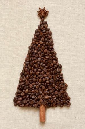 Christmas tree made of cinnamon sticks and coffee on linen background photo