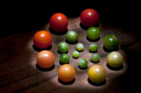 ripeness: Cherry tomatoes of different size and ripeness situated in circle, light brush technique Stock Photo