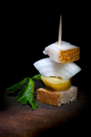 Canape with salted lard, onion, pickled cucumber, rye bread and parsley photo