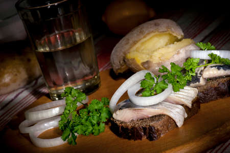 jacket potato: Sandwich with herring on rye bread, served with onion, jacket potato and glass of vodka