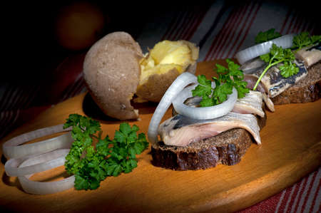 jacket potato: Sandwich made of herring on rye bread, served with onion, jacket potato and parsley Stock Photo
