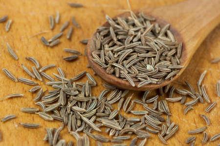caraway: Caraway (Carum carvi) seeds close up on cutting board Stock Photo