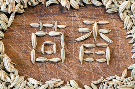 fennel seeds: Fennel written in Chinese characters with fennel seeds on wood close up Stock Photo