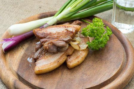 Fried Streifen mager (fatback) serviert mit gebratenen und frische junge Zwiebel auf hölzernen Schneidebrett Lizenzfreie Bilder