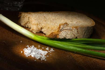 Scheibe Roggenbrot mit jungen grünen Zwiebeln und grobem Salz auf hölzernen Schneidebrett Lizenzfreie Bilder