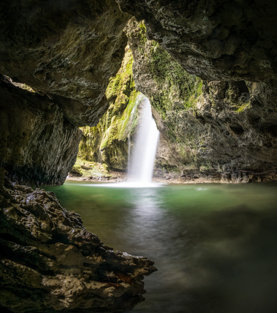 Waterfall grotto with moss covered rocks