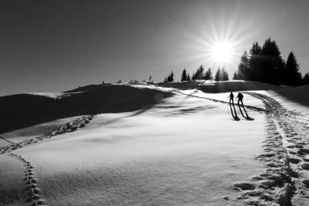 Two ski hikers walking towards the summit cross Stock Photo