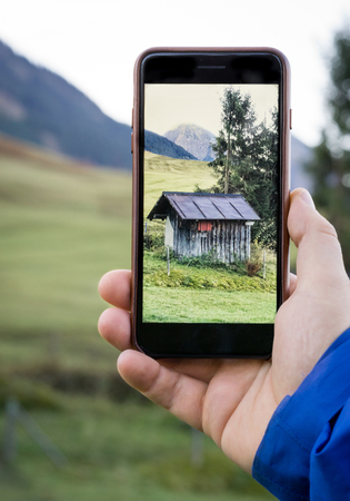 documented: Taking photo of a mountain hut with smartphone