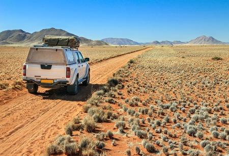 Pickup truck driving on desert road towards the Tiras mountains Standard-Bild