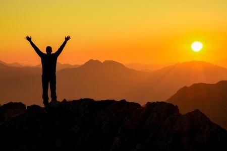 Happy success winning man arms up on mountain at sunset Standard-Bild
