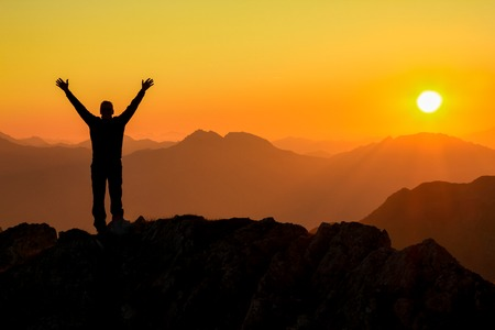 Happy success winning man arms up on mountain at sunset Stock Photo