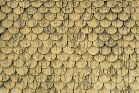 Old rustic wood tiling roof wall texture. Yellow weathered background. Stock Photo