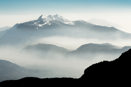 iluminado a contraluz: Spectacular view of mountain ranges silhouettes and fog in valleys.