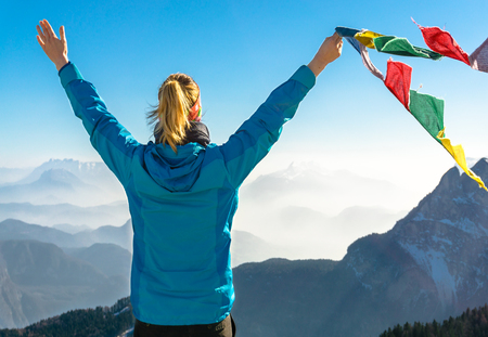 Happy success winning woman on summit arms up holding flag. Stock Photo