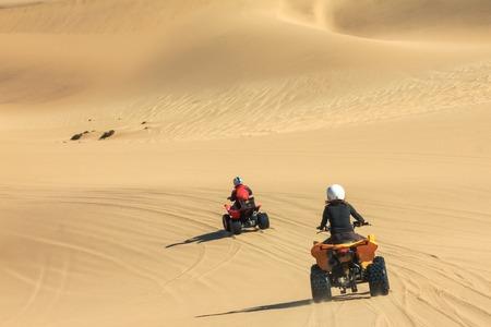 Quad personas de conducción - dos ciclistas felices en el desierto de arena. Foto de archivo