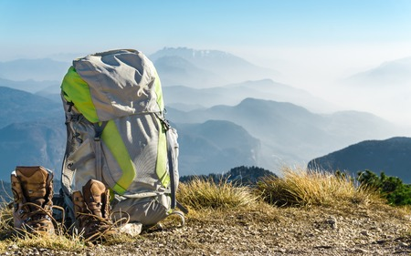 Hiking equipment. Backpack and boots on top of mountain. Standard-Bild