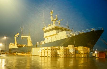 Fishing trawler ship at dock by night in drizzling rain