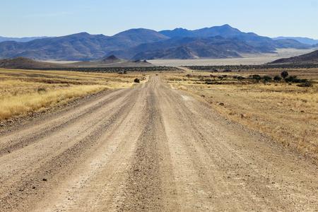 Strada sconnessa verso le montagne e attraverso prati aridi del deserto.