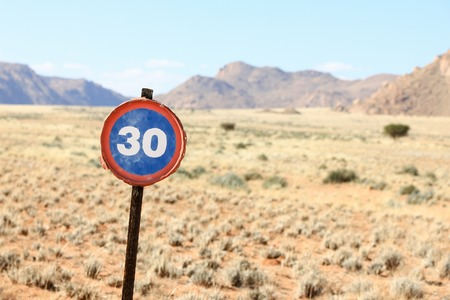 Old speed road sign in desert and mountain landscape