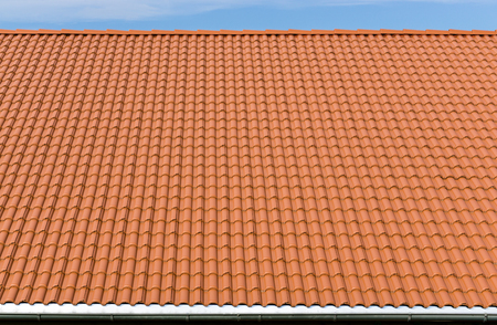 New and clean red tiles roof with rain pipe