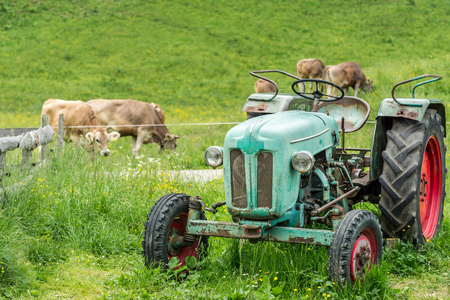 rusts: Old tractor on meadow. Beautiful mountain view in the Alps Stock Photo