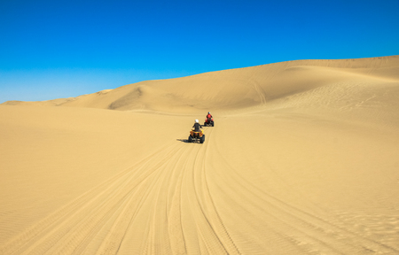 Quad driving people - two happy bikers in sand desert. Stock Photo