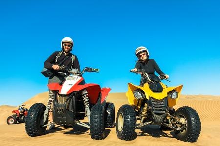 Quad rijden mensen - gelukkige lachende paar fietsers in zandwoestijn. Stockfoto