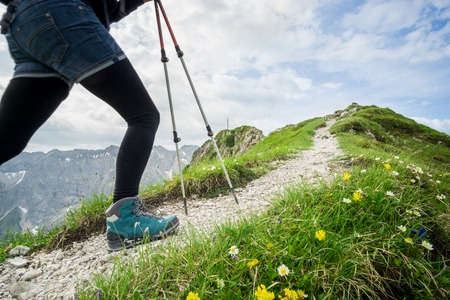Woman running on narrow mountain trail with hiking poles.