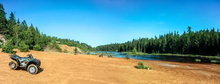 Personas que conducen cuatrimotos ATV en la playa de arena en el lago