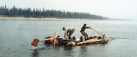 Two men rowing on self-made timber raft. Vintage expedition. Alaska. Stock Photo