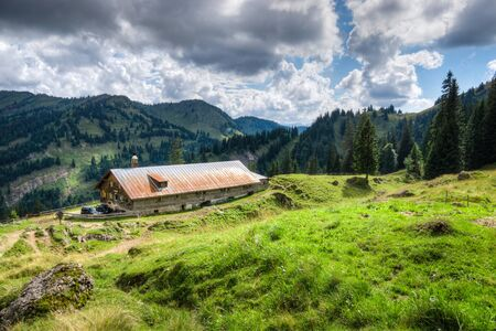 Old alpine hut with meadow in the Alps. Bavaria, Allgau, Germany. Traditional agriculture in the mountains. Stock Photo