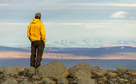 산에 서 서, 눈 덮인 산 범위쪽으로 편안 하 게 찾고 남자.